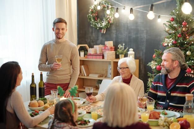 Веселый молодой человек с бокалом вина, поджаренным за сервированным столом перед его семьей во время рождественского ужина дома