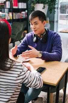 カフェのテーブルに座って、若い女性と話している間身振りで示す首にヘッドフォンを持つ陽気な若い男