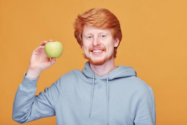 Веселый молодой человек со здоровой улыбкой держит яблоко бабушки смит и смотрит на вас, стоя у желтой стены