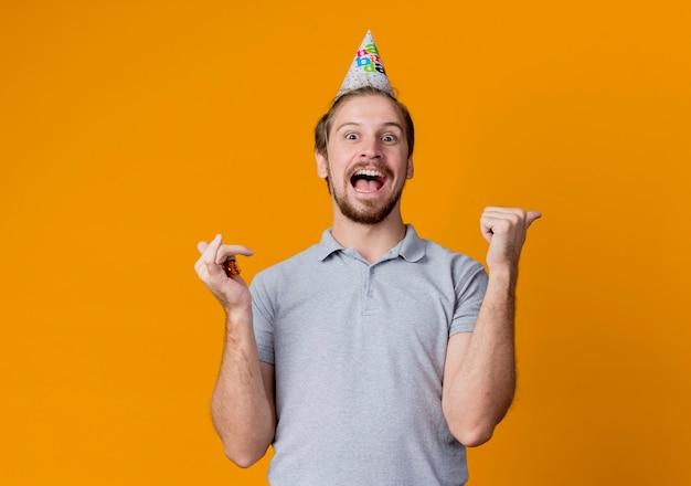 Giovane allegro con cappuccio di festa che celebra la festa di compleanno pazzo felice ed emozionato in piedi sopra la parete arancione