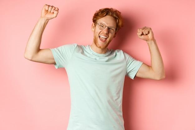 幸せそうに見える赤い髪の陽気な若い男、拳ポンプジェスチャーで手を上げ、成功を祝って、チャンピオンのように感じ、勝利し、ピンクの背景の上に立っています