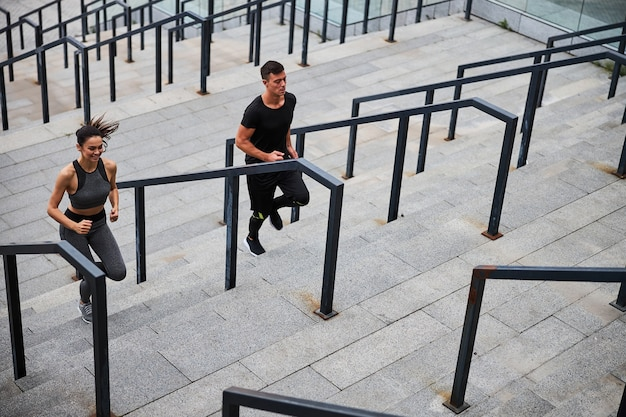 Cheerful young man and woman doing cardio workout and running upstairs in city centre