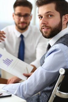 Cheerful young man working with colleague in office