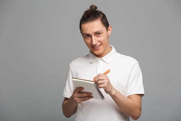 Веселый молодой человек написание заметок в записной книжке.