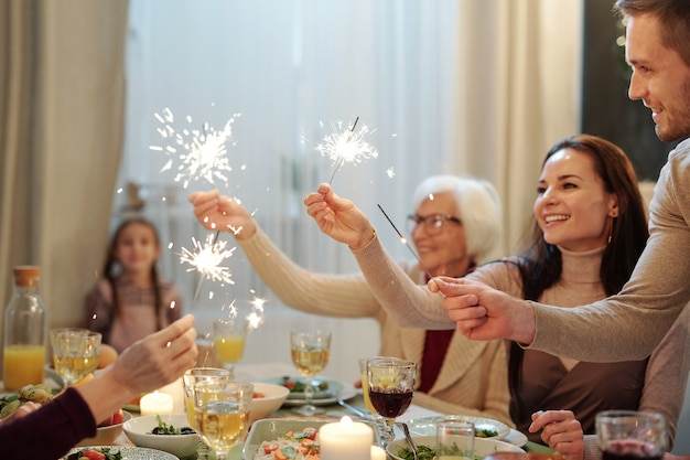 Cheerful young and mature adults holding sparkling bengal lights over served festive table during christmas dinner
