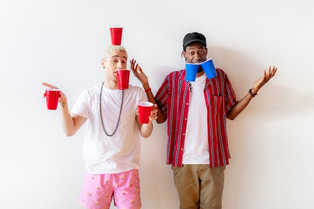 Cheerful young men holding cups