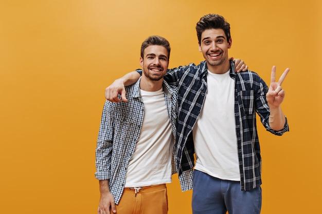 Веселые юноши в клетчатых синих рубашках, белых футболках и ярких штанах позируют на оранжевой стене в отличном настроении и улыбаются.