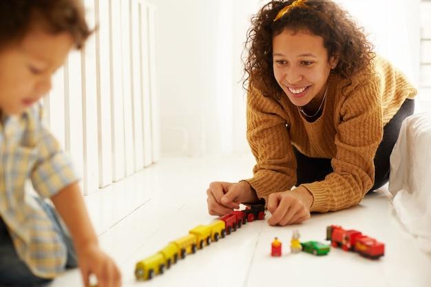 Allegro giovane madre di razza mista in abiti casual che si siede sul pavimento con il suo bambino che gioca con la ferrovia del giocattolo insieme. donna carina che gode della sua maternità, trascorrendo del tempo con il figlio. messa a fuoco selettiva