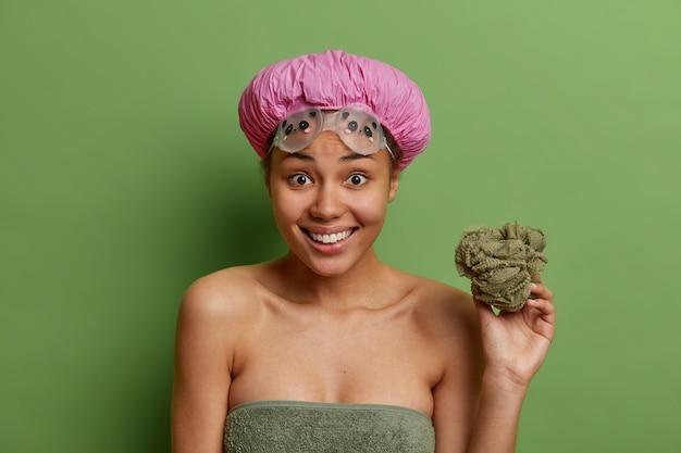 쾌활한 젊은 혼혈 여성 미소는 광범위하게 녹색 벽에 고립 된 피부와 몸에 대한 욕실 caes에서 위생 절차를 거 치러 샤워를 할 목욕 스폰지를 보유하고 있습니다.
