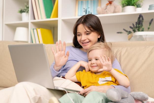 ビデオチャットで父親と話している間、ソファに座って手を振っている陽気な若い母と息子