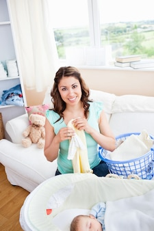 Cheerful young mother doing the laundry while her baby is sleeping in the livingroom