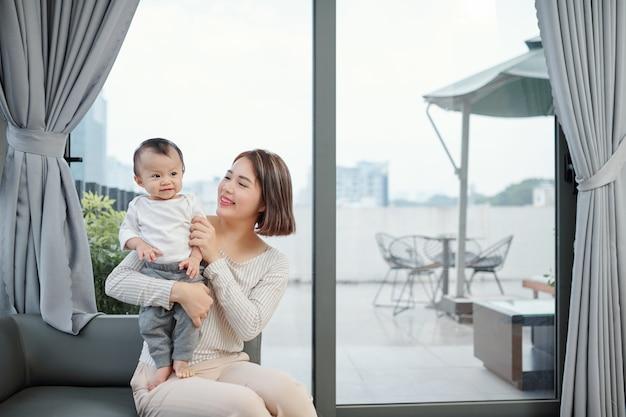 家で愛らしい小さな赤ちゃんと遊ぶ陽気な若い母親