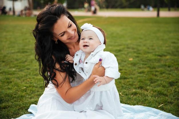Веселая молодая мать сидит с маленькой дочерью на открытом воздухе