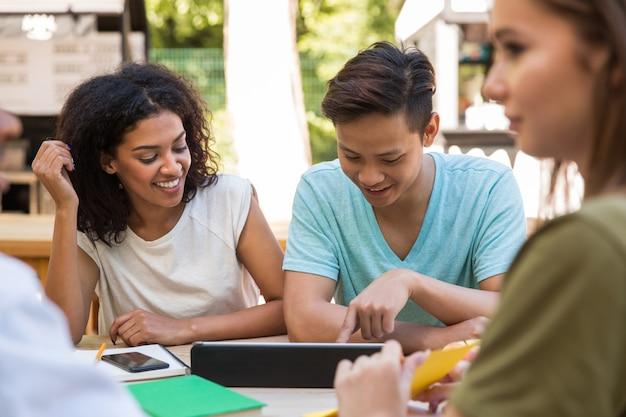 Giovani studenti multietnici allegri degli amici all'aperto facendo uso della compressa