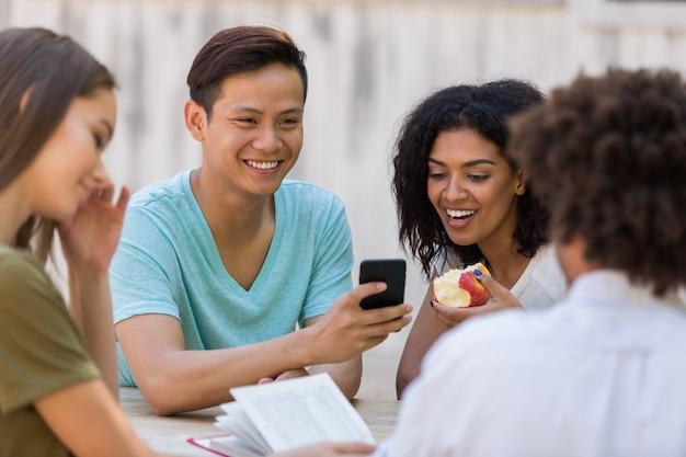 전화를 사용하여 이야기하는 친구 학생의 쾌활한 젊은 다민족 그룹