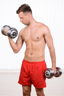 Cheerful young muscular man training using dumbbells.