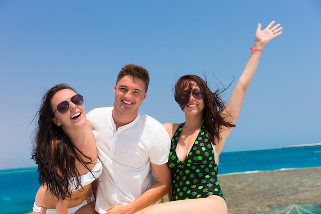 화창한 여름날 요트에 서서 즐거운 시간을 보내는 쾌활한 젊은이들, 머리카락이 자라는 바람, 배경의 아름다운 바다