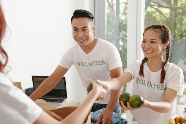 커뮤니티 센터에서 도움이 필요한 사람들을 위해 종이 봉지에 신선한 과일을 포장하는 쾌활한 젊은이들