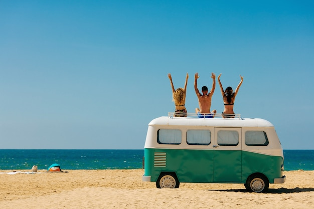 Cheerful young people relaxing on top of retro bus near sea