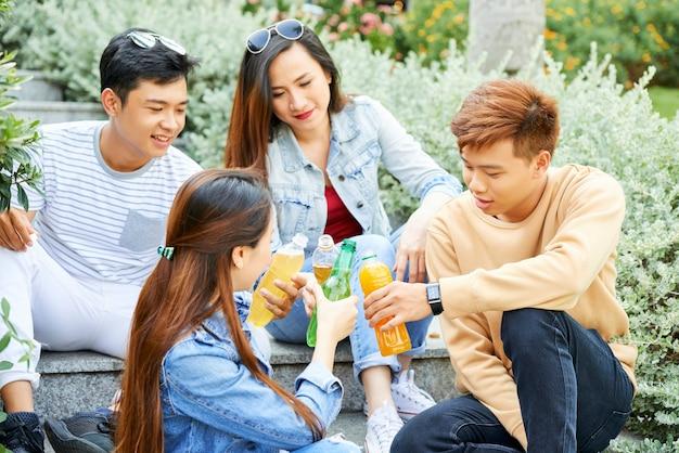 야외에서 쉬고 있는 쾌활한 젊은이들과 상쾌한 차가운 음료수 병