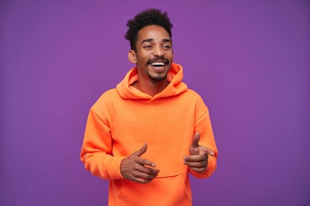 陽気な若いかなりひげを生やした黒髪の黒い肌の男は、幸せに笑い、上げられた人差し指を脇に見せ、カジュアルなスポーティな服装で紫に立ち向かいます