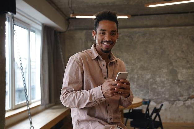 Allegro giovane maschio piuttosto barbuto con pelle scura che tiene il cellulare nelle mani e che guarda l'obbiettivo felicemente con un ampio sorriso sincero, aspettando gli amici nel caffè della città in abiti casual