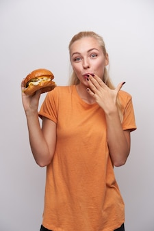 Cheerful young pretty blonde woman with casual hairstyle looking positively at camera and keeping hand on her mouth while tasting big fresh burger, standing against white background