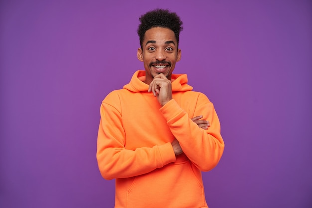Allegro giovane uomo bruna dalla pelle scura piuttosto castani con la barba che tiene la mano alzata sul mento e sorridente felicemente, isolato su viola in felpa con cappuccio arancione