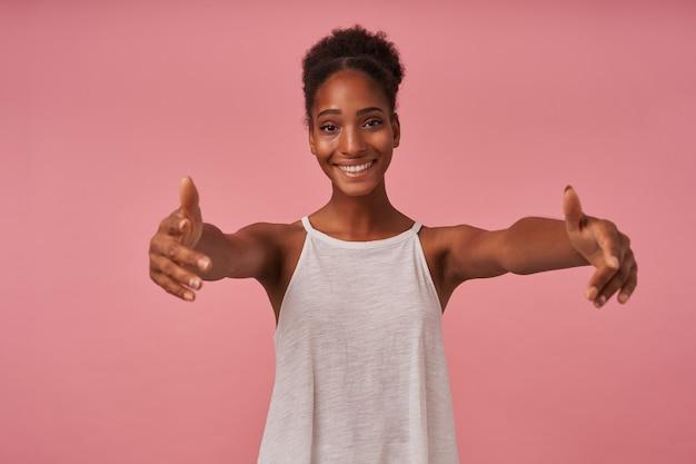 腕を広げてピンクの壁の上に立って、誰かに抱擁を与えるつもりで、正面で幸せそうに笑っている陽気な若いかわいい茶色の髪の巻き毛の女性 無料写真