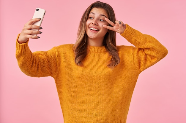 カジュアルな服装でピンクの上に立って、スマートフォンで自分の肖像画を作りながら、勝利のサインを顔に上げて手を上げる陽気な若いかわいい茶色の髪の女性