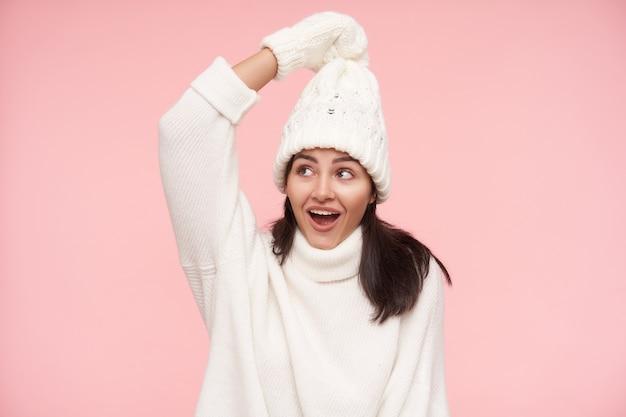 쾌활한 젊은 예쁜 갈색 머리 아가씨, 캐주얼 헤어 스타일이 그녀의 모자를 잡고 기꺼이 웃고있는 동안 그녀의 손을 유지하고 분홍색 벽 위에 절연