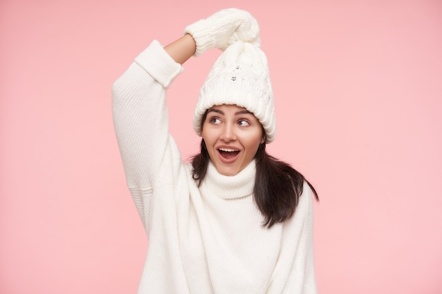 Cheerful young pretty brown haired lady with casual hairstyle keeping her hands raised while holding her hat and smiling gladly, isolated over pink wall