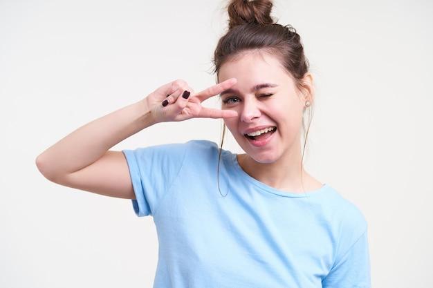 Веселая молодая симпатичная шатенка с прической булочки держит знак мира возле ее лица и с радостью подмигивает впереди, изолированной на белой стене