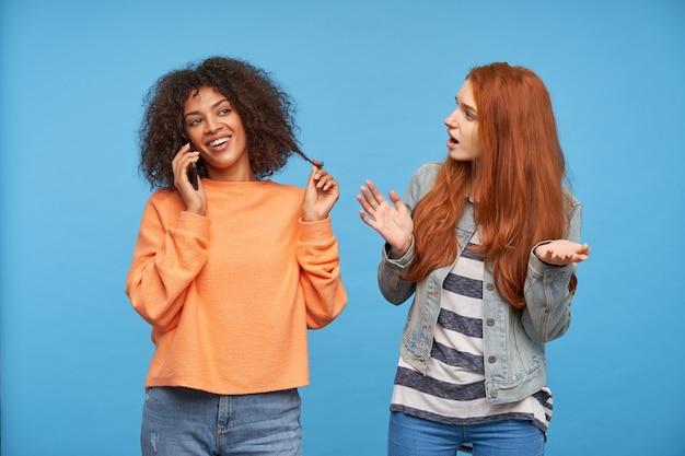 Allegro giovane donna bruna dalla pelle scura piuttosto riccia sorridente felicemente pur avendo una piacevole conversazione telefonica, in posa sopra la parete blu con donna attraente rossa confusa