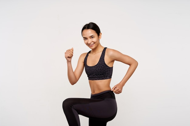 Веселая молодая довольно темноволосая женщина, одетая в спортивную одежду, с удовольствием улыбается спереди, делая физические упражнения, изолированные на белой стене