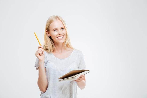 흰 벽에 고립 된 아이디어와 함께 노트북을 들고 쾌활 한 젊은 예쁜 여자
