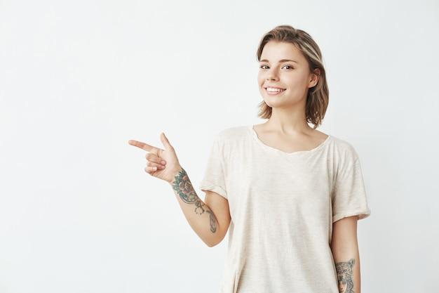 Жизнерадостная молодая милая девушка усмехаясь указывающ палец в сторону.