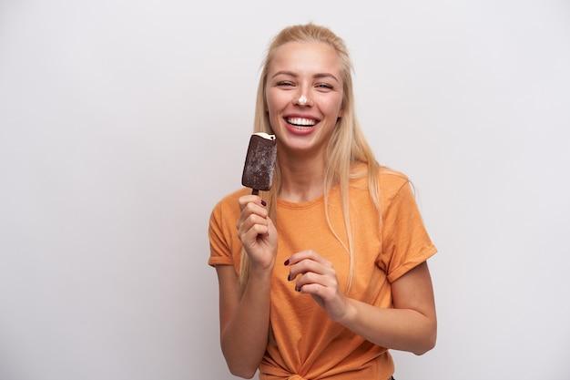 Allegro giovane donna bionda dai capelli lunghi con un sorriso piacevole scherzare con gelato sul bastone mentre in piedi contro uno sfondo bianco in abiti casual