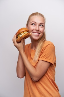陽気な若いかなり長い髪のブロンドの女性は、おいしいハンバーガーで手を上げて、白い背景の上にポーズをとって、魅力的な笑顔で幸せに脇を見てカジュアルな髪型
