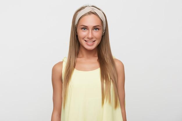 カジュアルな服装で白い背景の上に立って、魅力的な笑顔でカメラを喜んで見ているハチュラルメイクの陽気な若いかなり長い髪のブロンドの女性