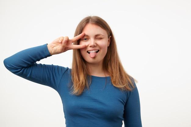 Веселая молодая довольно длинноволосая женщина поднимает руку с жестом победы к ее лицу и радостно показывает язык в камеру, стоя на белом фоне