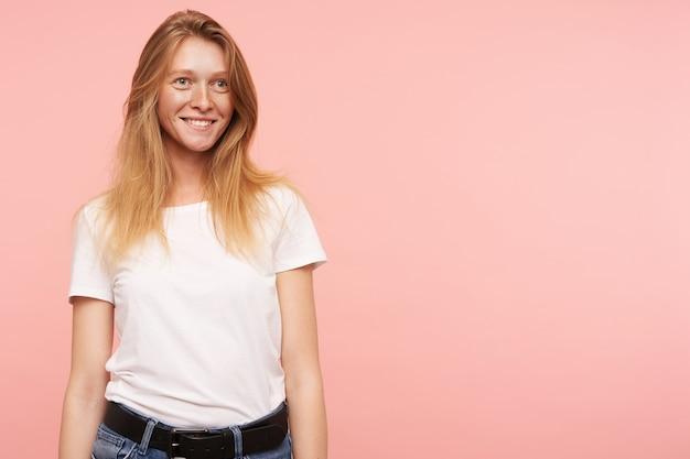 陽気な若いかなり長い髪の赤毛の女性は、ピンクの背景の上に立って、心地よい笑顔で前向きに脇を見て、体に沿って手を保ちます