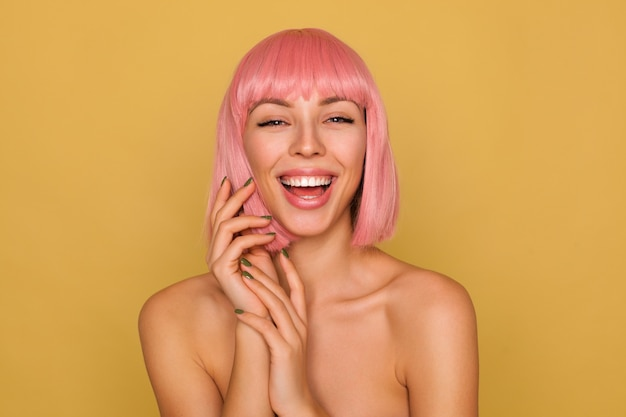 Cheerful young pretty pink haired woman laughing happily while looking  and folding raised hands while posing over mustard wall