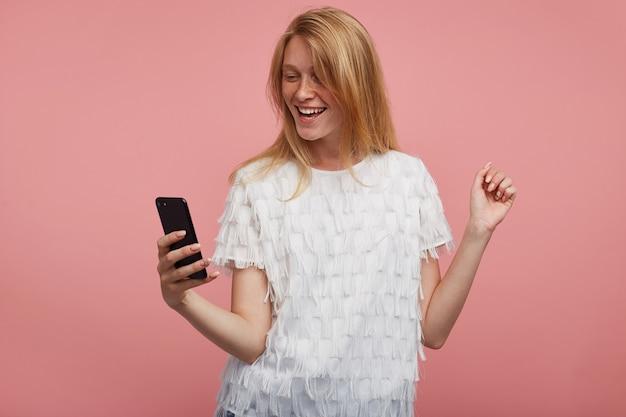 쾌활한 젊은 예쁜 빨간 머리 여성 캐주얼 헤어 스타일이 제기 손에 휴대 전화를 유지하면서 자신의 사진을 만들고 긍정적으로 웃고, 분홍색 배경 위에 절연