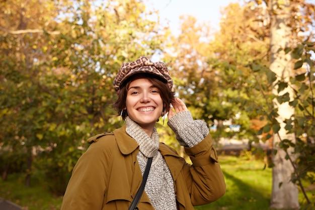 Allegro giovane donna bruna dai capelli corti che indossa trincea, maglione lavorato a maglia e cappello con stampa leopardata mentre posa sul giardino della città, essendo di buon umore e sorridendo ampiamente
