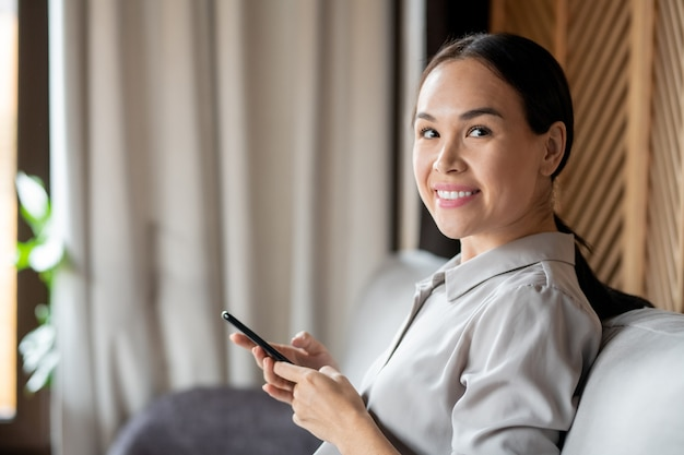Cheerful young pretty woman in casualwear looking at you while sitting on couch in front of camera