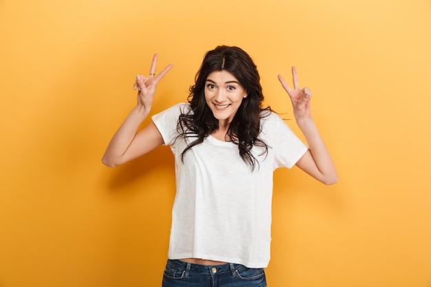 平和のジェスチャーを示す陽気な若いきれいな女性。