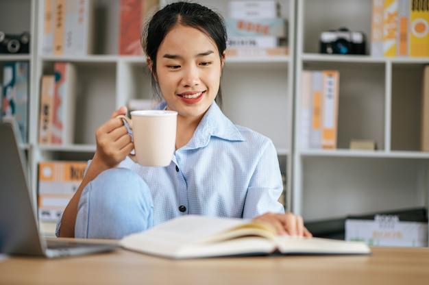 Allegra giovane bella donna seduta e usa il computer portatile e il libro di testo per lavorare o imparare online, tenendo in mano una tazza di caffè e sorridendo felice