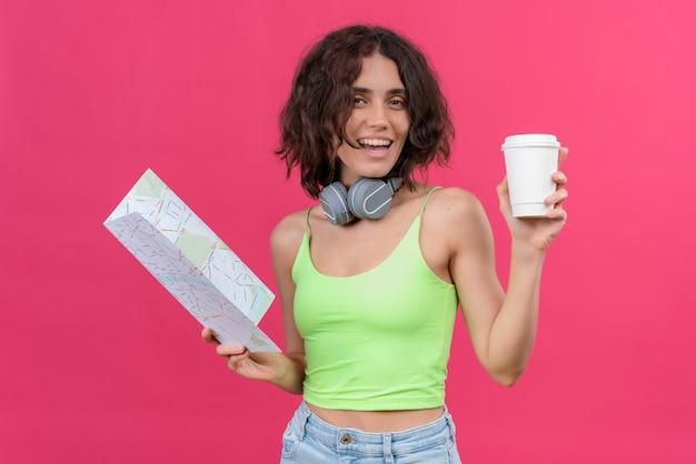 Una giovane donna graziosa allegra con i capelli corti in top corto verde in cuffie che tengono tazza di caffè di plastica