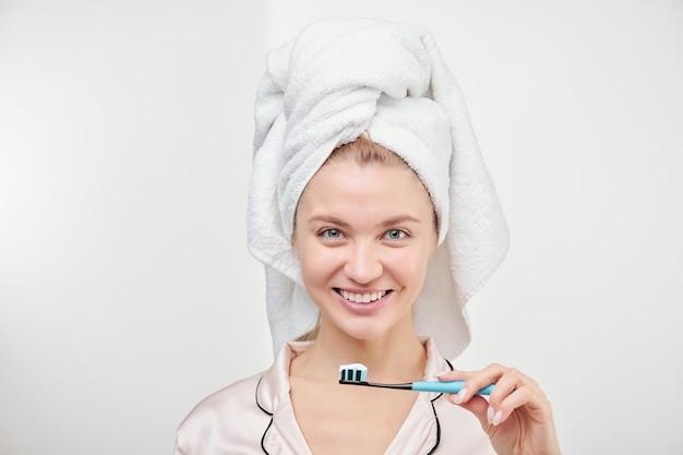 孤立して立っている間彼女の口で歯ブラシを保持している歯を見せる笑顔で陽気な若いきれいな女性